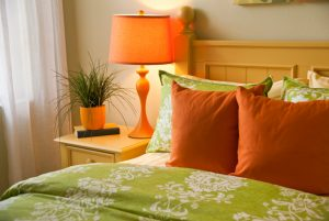 Bedroom with bedside table and lamp, colorful pillows and bedspread, and sheer curtains.
